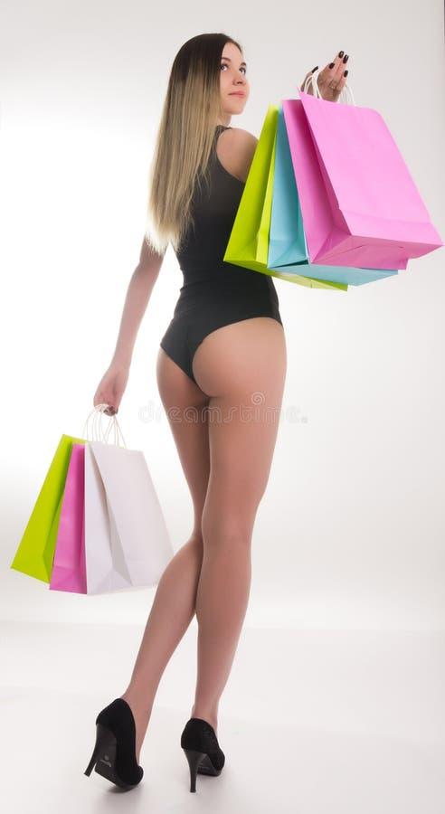 Sacos de compra da terra arrendada da mulher da compra Close up dos pés bonitos das mulheres em um maiô e nos saltos altos, guard imagem de stock
