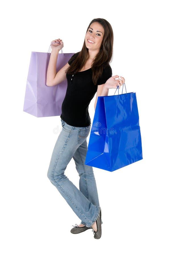 Sacos de compra felizes da terra arrendada da mulher nova, isolados imagens de stock