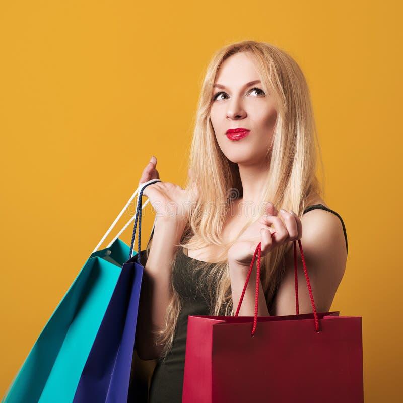 Sacos de compra felizes da terra arrendada da mulher Menina loura que aprecia vendas sazonais Tempo da compra Consumição, compra, imagem de stock