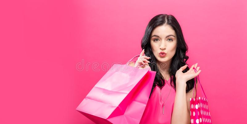 Sacos de compra felizes da terra arrendada da mulher nova imagem de stock