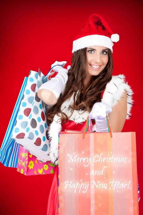 Sacos de compra 'sexy' da terra arrendada da mulher de Santa fotos de stock