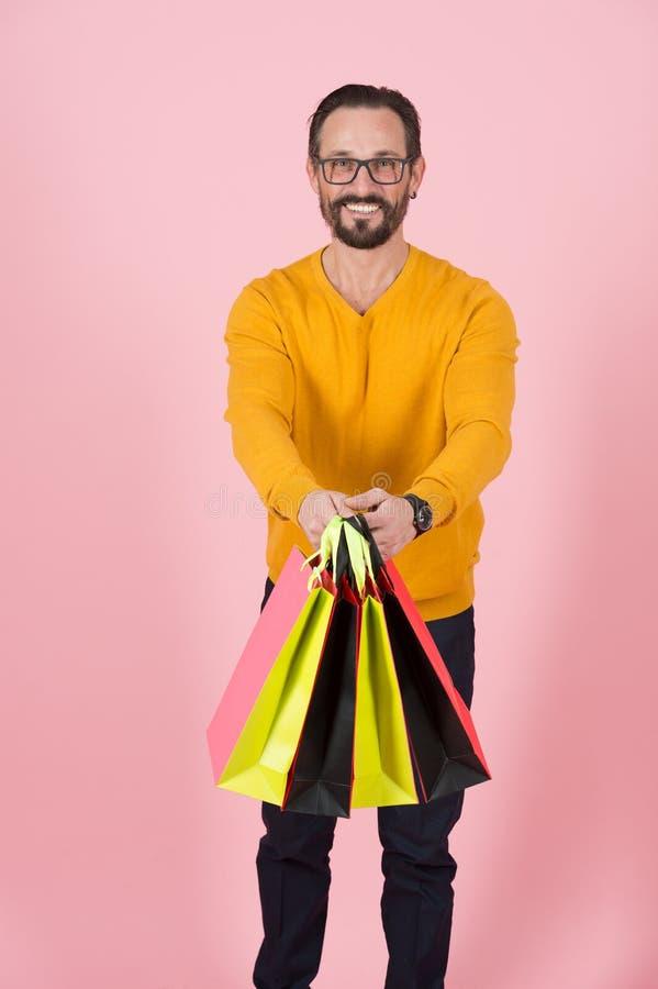 Sacos de compras à disposição de indivíduo sorrido considerável nos vidros Sacos de papel coloridos disponivéis do homem no casac fotos de stock