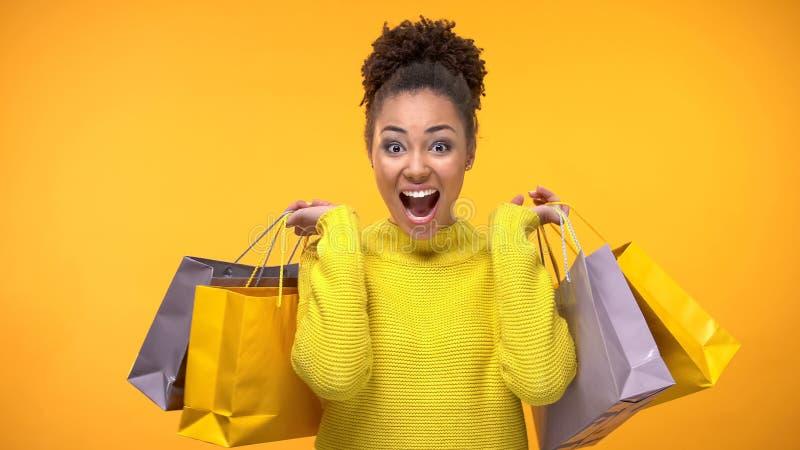 Sacos de compras afro-americanos felizes da mulher, desconto sazonal, venda dos feriados fotos de stock