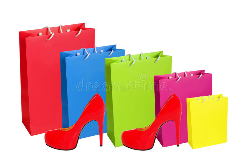 Sacos de compras de papel coloridos e sapata vermelha de madeira isolados no wh fotos de stock royalty free