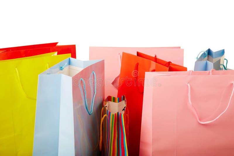 Sacos de compras de papel coloridos no branco imagem de stock royalty free