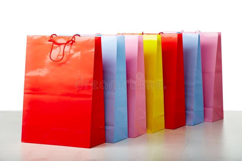 Sacos de compras de papel coloridos no branco imagem de stock
