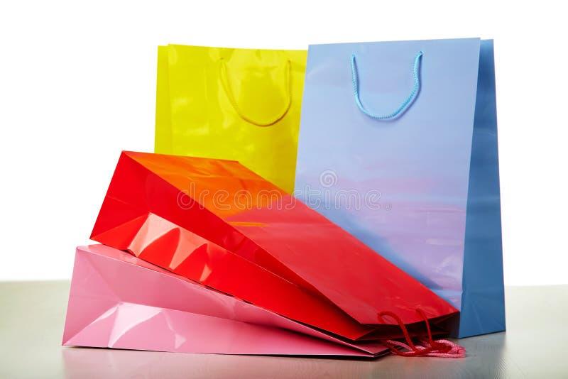 Sacos de compras de papel coloridos no branco fotografia de stock royalty free
