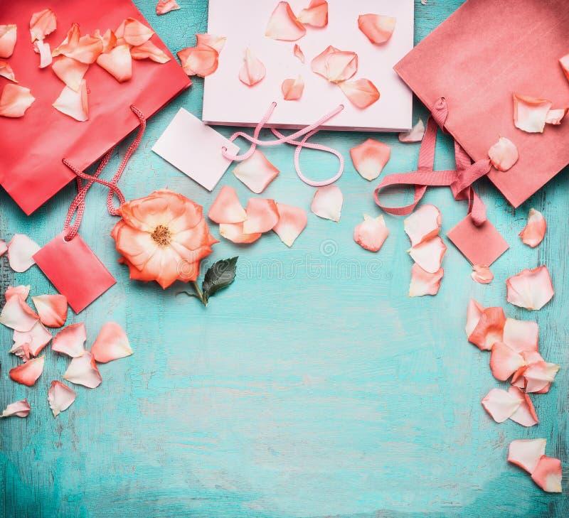 Sacos de compras de papel pálidos cor-de-rosa com rosas e etiquetas vazias no fundo azul de turquesa, vista superior imagens de stock