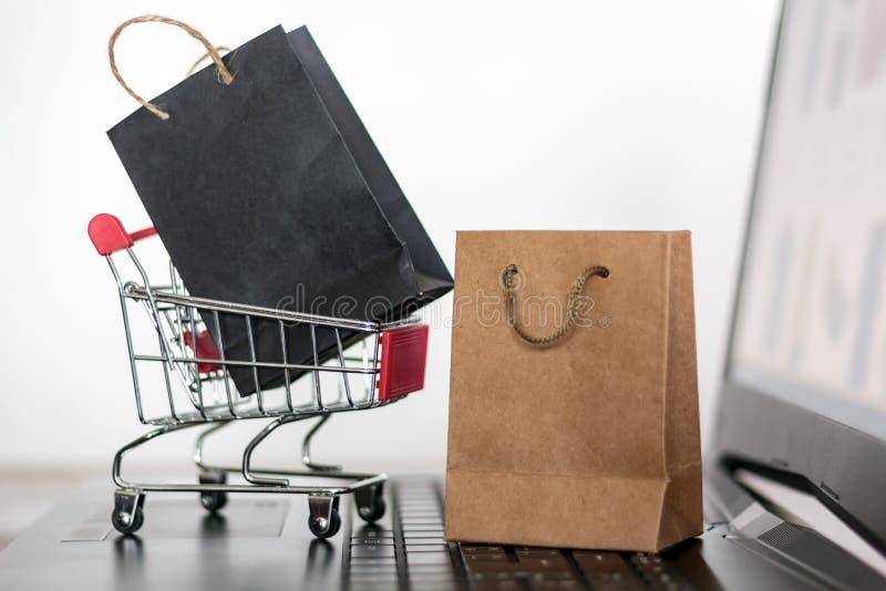 Sacos de compras e carrinho no teclado do computador Compras online, conceito de comércio eletrônico imagem de stock royalty free