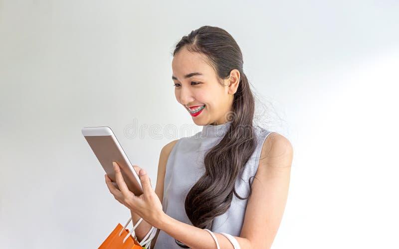 Sacos de compras e telefone celular guardando f?meas novos felizes Uso asiático da mulher do telefone celular e do saco de compra imagem de stock royalty free