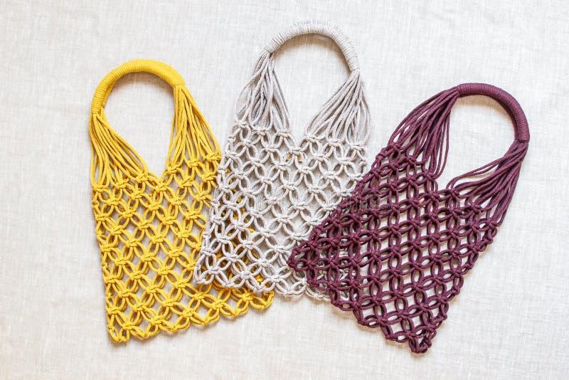 Sacos de compras feitos a mão do macramê no fundo claro Eco amig?vel embroidery Conceito moderno do ver?o foto de stock royalty free