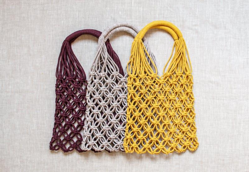Sacos de compras feitos a mão do macramê no fundo claro Eco amig?vel embroidery Conceito moderno do ver?o fotos de stock