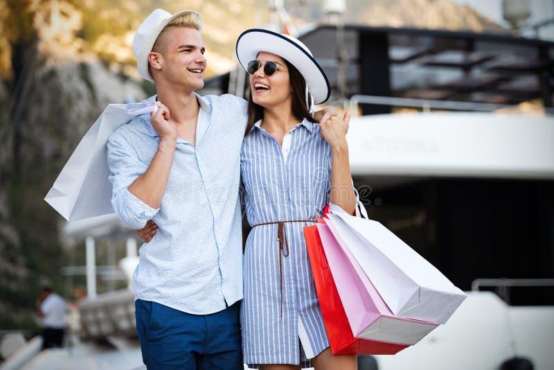 Sacos de compras levando de amor bonitos dos pares e apreciação junto fotografia de stock