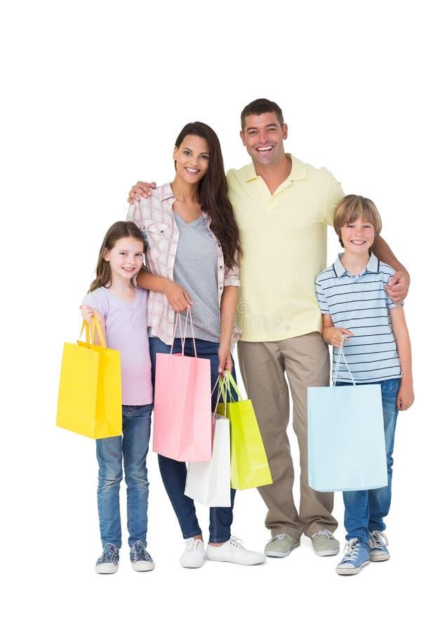 Sacos de compras levando da família feliz imagens de stock