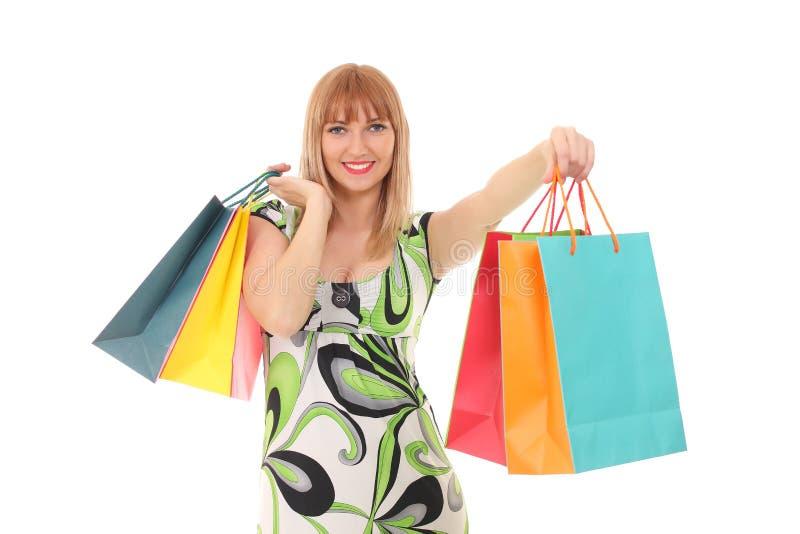Sacos de compras levando da jovem mulher contra o fundo branco foto de stock