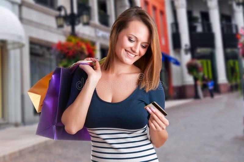 Sacos de compras levando da mulher e guardar um cartão de crédito fotos de stock