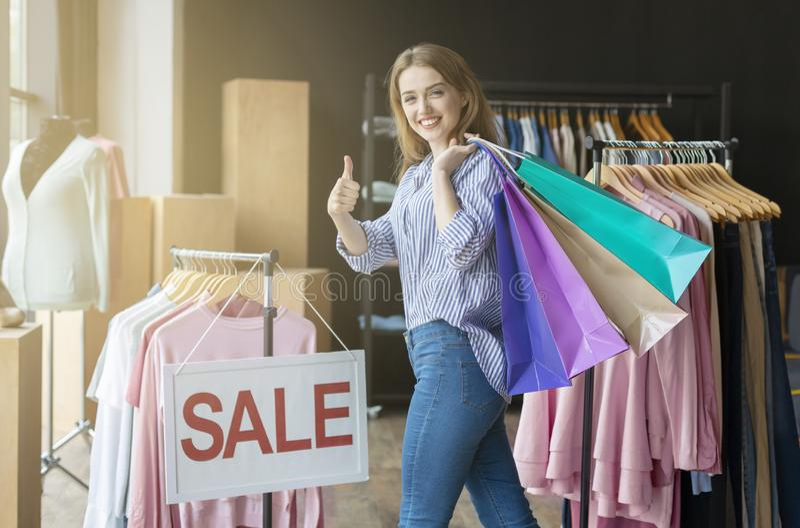 Sacos de compras levando shopaholic felizes no ombro, mostrando o polegar acima foto de stock royalty free