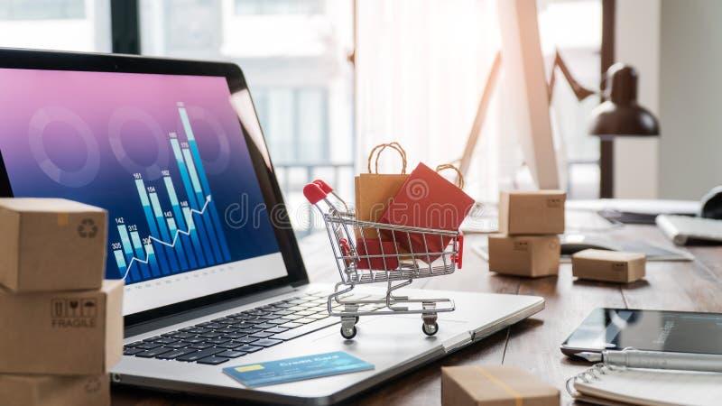 Sacos de compras no carrinho de compras e no cartão de crédito no portátil com as caixas de papel na tabela e o gráfico do cresci imagem de stock