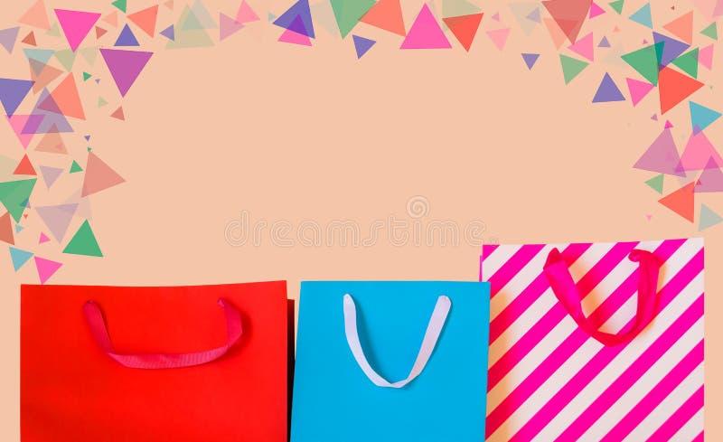 Sacos de compras de papel coloridos no fundo pastel fotografia de stock