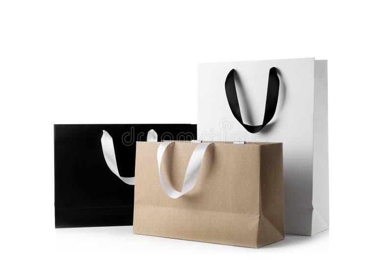 Sacos de compras de papel com os punhos da fita no fundo branco imagens de stock