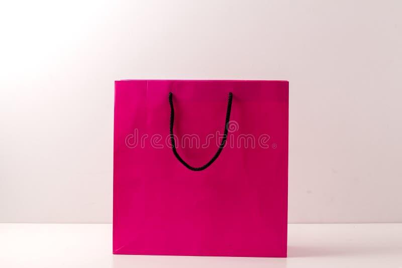 Sacos de compras de papel cor-de-rosa isolados no branco fotos de stock royalty free
