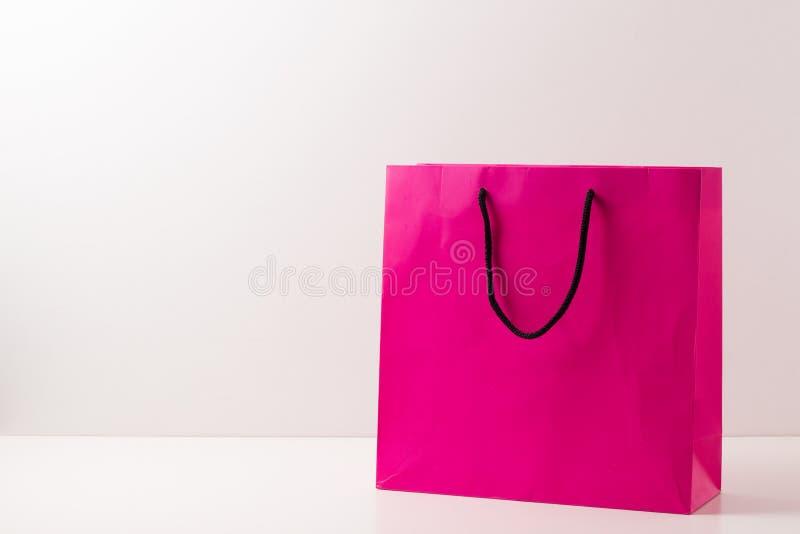 Sacos de compras de papel cor-de-rosa isolados no branco fotos de stock
