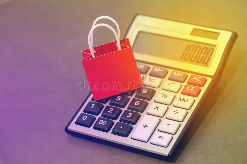 Sacos de compras de papel vermelhos pequenos do close up na calculadora Ideia de março imagem de stock
