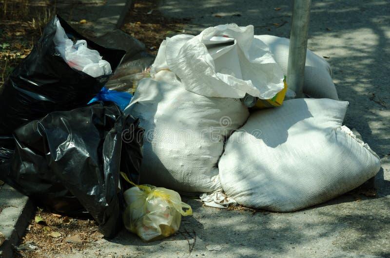 Sacos de lixo completamente da maca que polui a rua na cidade foto de stock