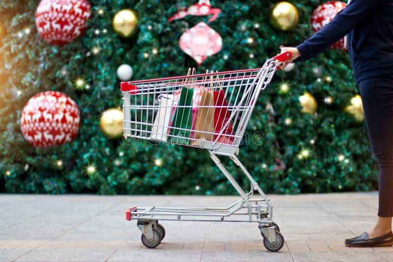 Sacos de papel compra-fêmeas do cliente do Natal no carro imagens de stock royalty free