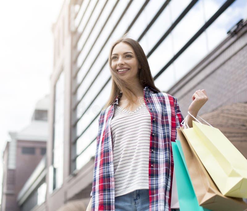 Sacos de papel levando da jovem senhora bonita, andando abaixo da rua imagens de stock royalty free