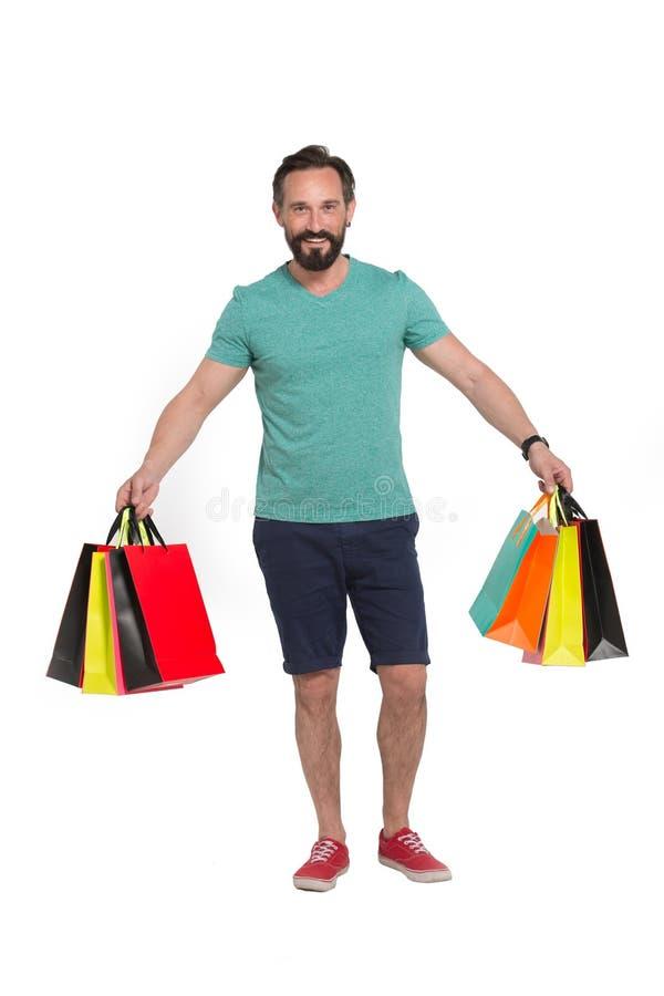Sacos de papel levando do homem alegre quando compra indo fotografia de stock