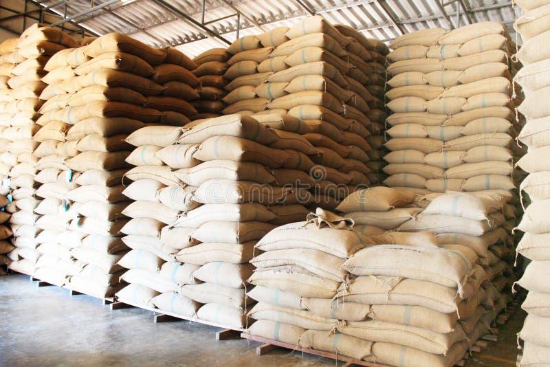 Sacos del cáñamo que contienen el arroz imagenes de archivo
