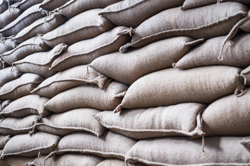 sacos del cáñamo que contienen el grano de café en almacén sacos apilados adentro fotografía de archivo