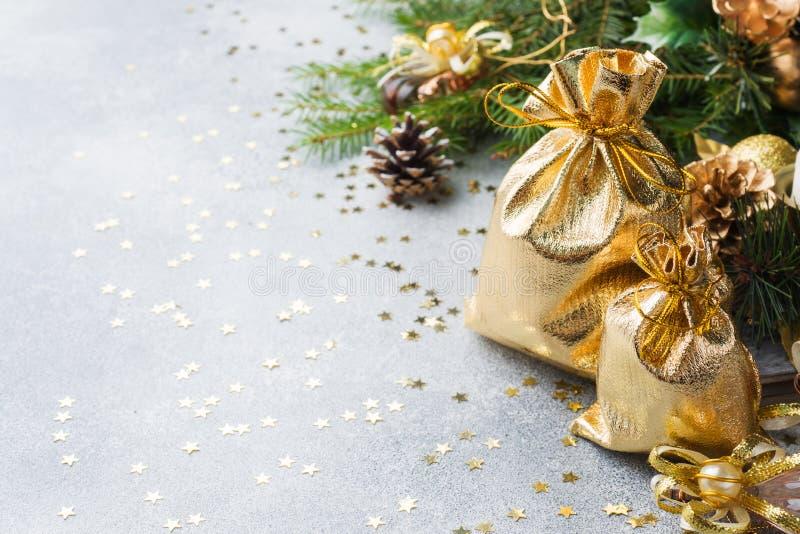 Sacos do ouro com os presentes do Natal no fundo de árvores de Natal e do fundo cinzento das decorações Conceito dos cumprimentos foto de stock royalty free
