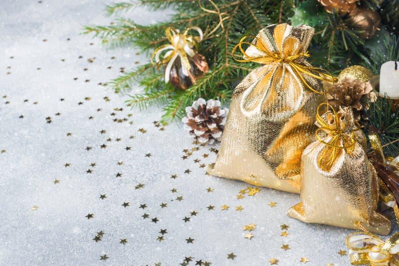 Sacos do ouro com os presentes do Natal no fundo de árvores de Natal e do fundo cinzento das decorações Conceito dos cumprimentos fotos de stock
