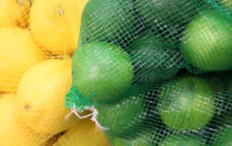 Sacos de rede com limões e cais fotos de stock