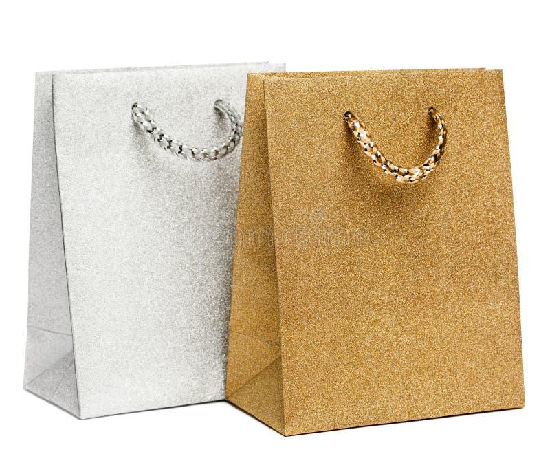 Sacos dourados e de prata do presente no branco imagens de stock