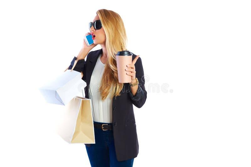 Sacos e smartphone shopaholic louros da mulher imagem de stock