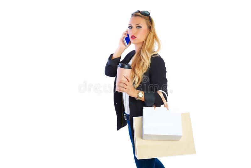 Sacos e smartphone shopaholic louros da mulher foto de stock
