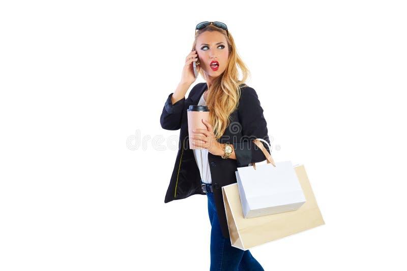 Sacos e smartphone shopaholic louros da mulher imagem de stock royalty free
