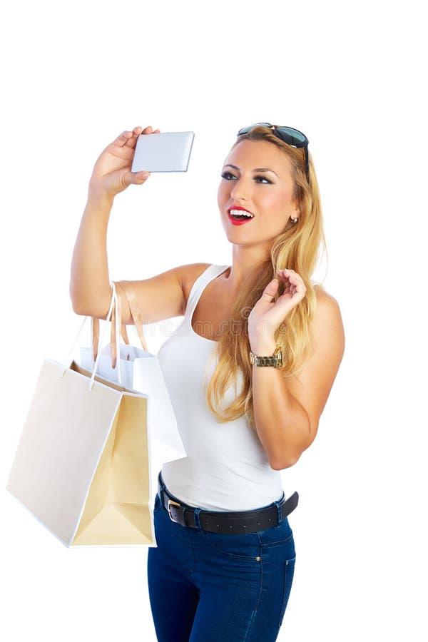Sacos e smartphone shopaholic louros da mulher imagens de stock