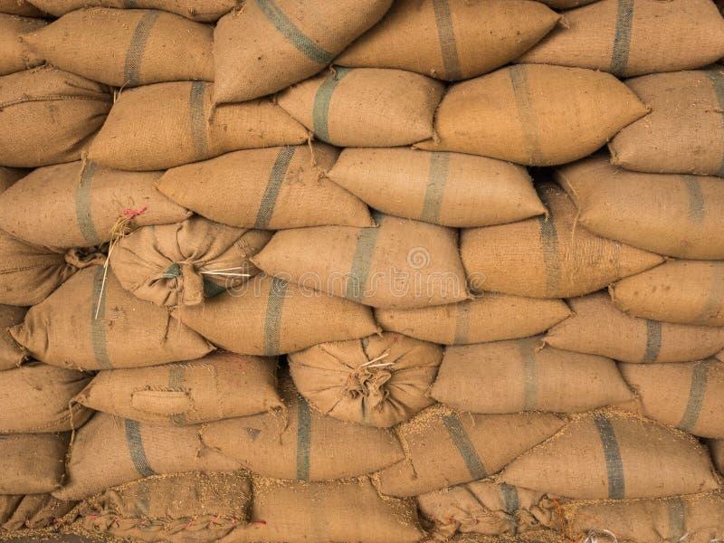 Sacos viejos del cáñamo que contienen el arroz colocado apilado imagen de archivo libre de regalías