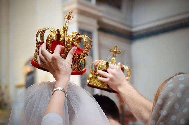 Sacral details of wedding ceremony - bridal crowns above head. Wedding in Orthodox Church - witnesses held bridal crowns over the head royalty free stock images