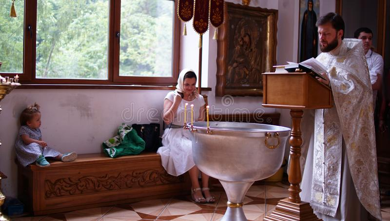 The sacrament of baptism. Christening the baby. Child, priest and parishioners stock images