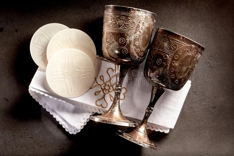 Sacramental bread and silver chalice cups. Consecrated Sacramental bread or Hosties and silver chalice cups for the wine symbolising the body and blood of the royalty free stock photos