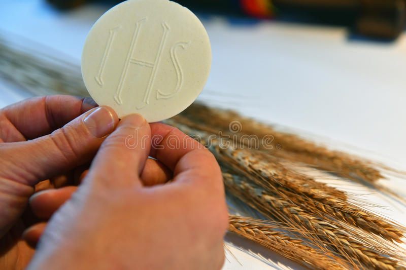 Sacramental bread and wheat. Hands holding sacramental bread and wheat in the background royalty free stock photography