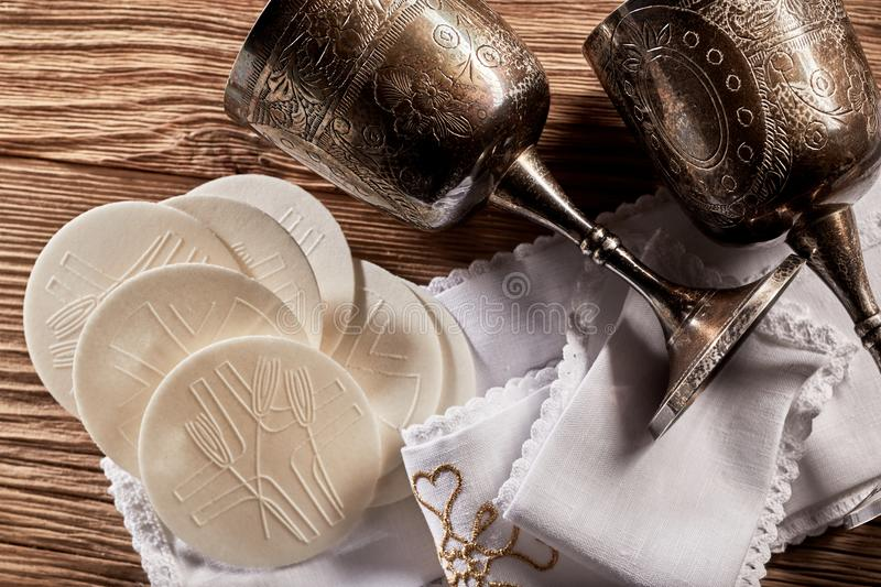 Sacramental Hosties with silver chalice cups. For the red wine symbolising the body and blood of the resurrected Christ for the Holy Communion church service stock photos