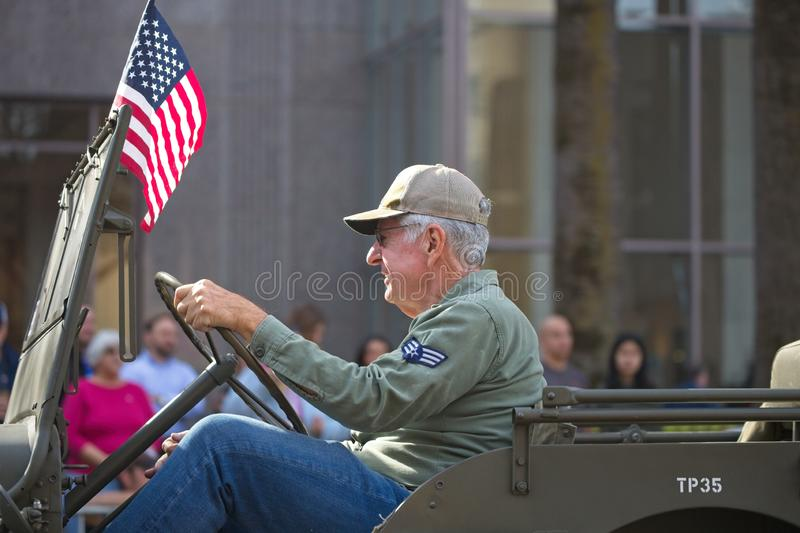 Sacramento Veterans Day Parade. Military jeep. Sacramento, California, United States - November 11, 2019: Veterans Day Parade. A veteran soldier riding along the stock images