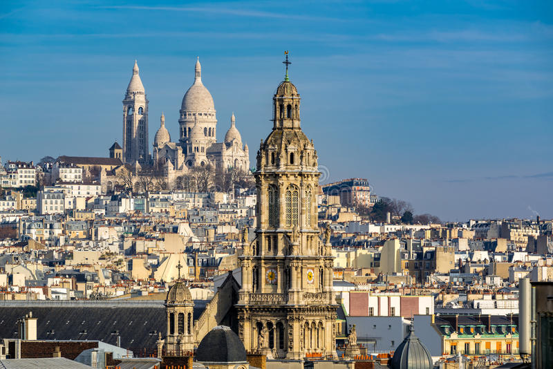 Sacre Coeur Basilica in Montmartre and Trinity Church. Paris, France. Rooftops of Paris with view of the Sacre Coeur Basilica in Montmartre and the Trinity royalty free stock image