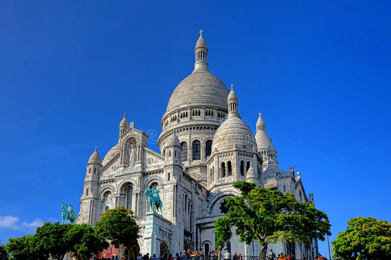 The Sacre Coeur Basilica on Paris Butte Montmartre. The Sacre Coeur Basilica of the Sacred Heart of Paris tourist landmark Roman Catholic church at the summit of stock photos